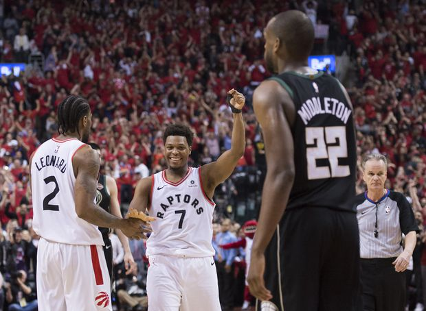 ac85dbd49d8 Kyle Lowry reacts with teammate Kawhi Leonard as Milwaukee Bucks forward  Khris Middleton (22) looks on during the final seconds of the second half  NBA ...