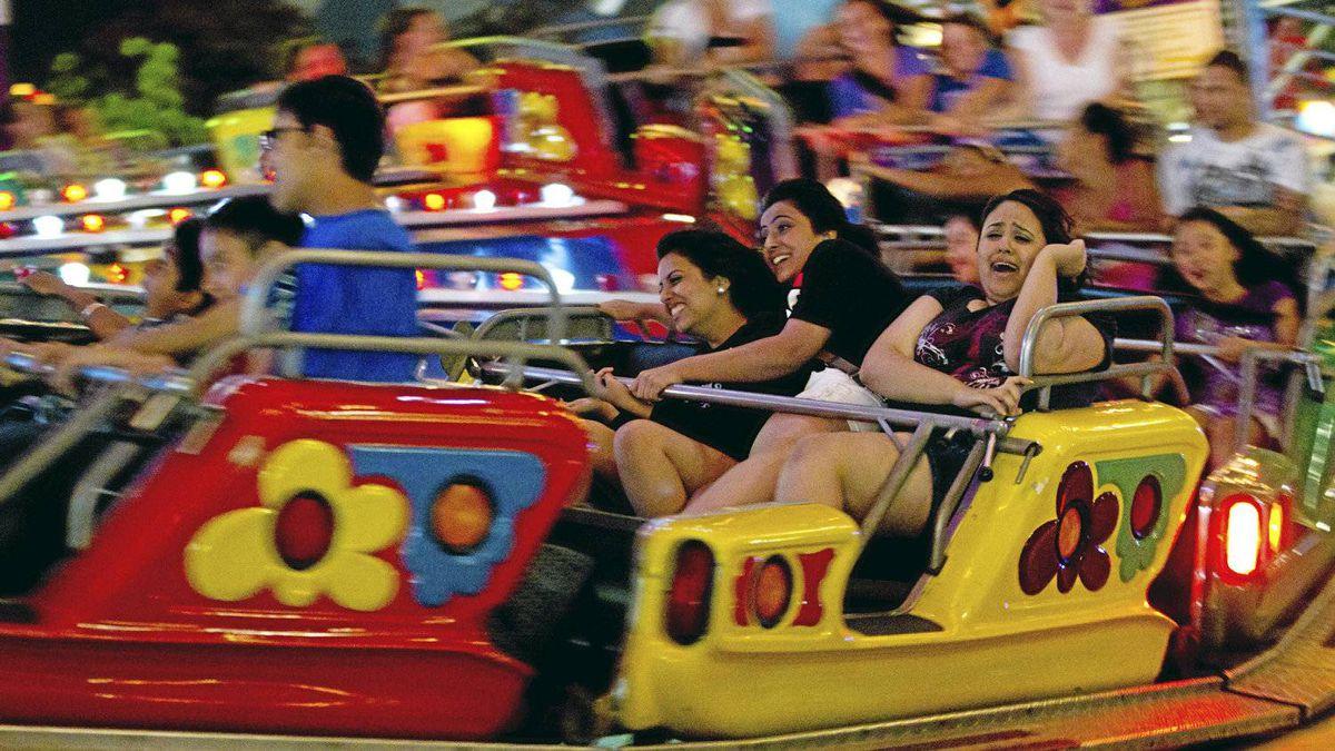 Sisiters Karen, left, and Ashveen Gill along with cousin Aman Heer, right, ride the Music Express at the Pacific National Exhibition in Vancouver, Aug. 20, 2011.