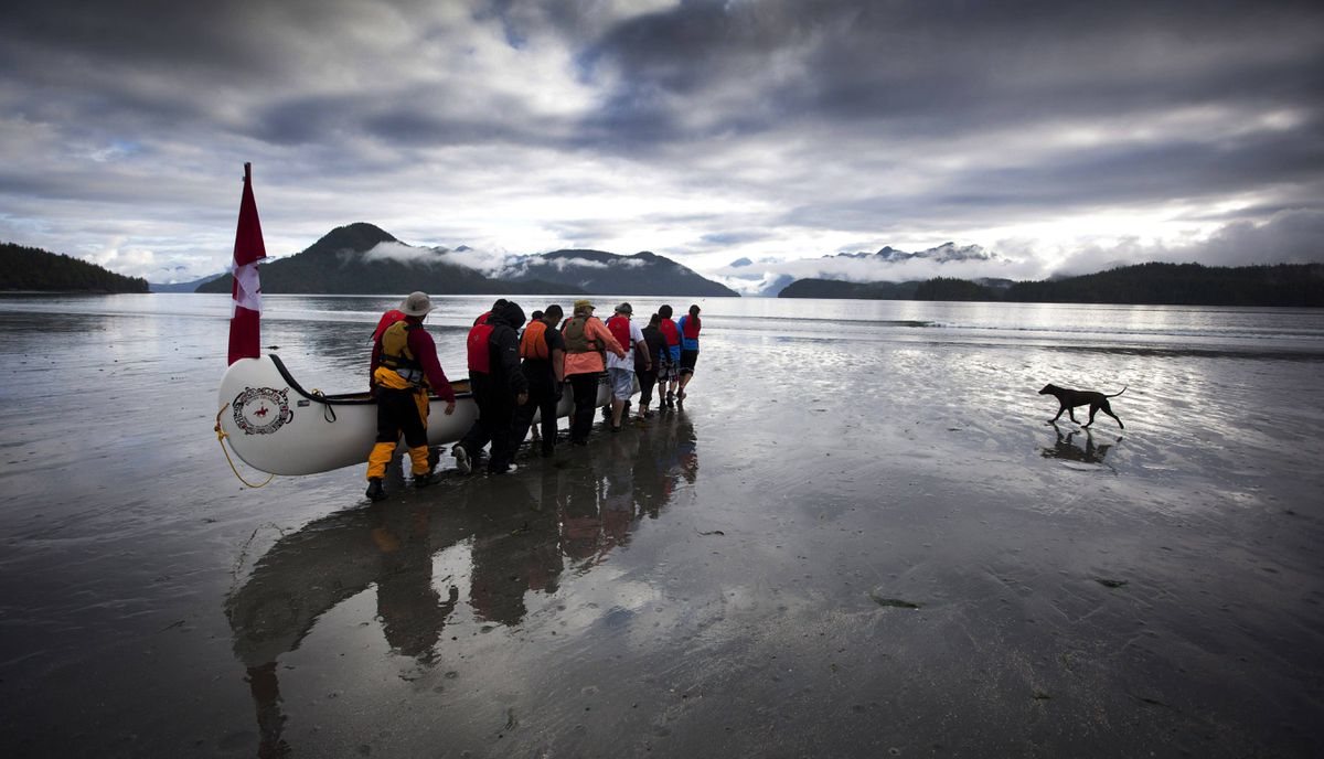 One canoes from the Pulling Together journey makes their way down to the water. This year, 19 thirteen-person canoes are making the eight-day journey, visiting remote native villages between Tofino and Port Alberni.