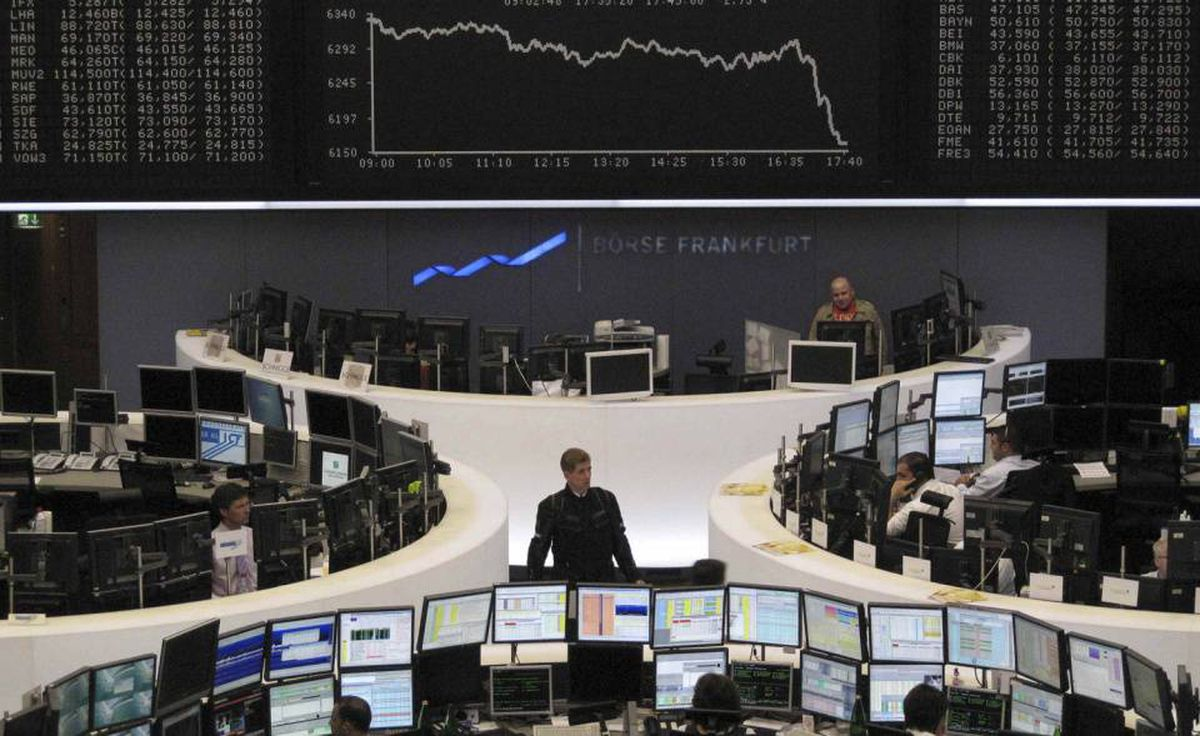Traders are pictured at their desks in front of the DAX board at the Frankfurt stock exchange April 27, 2010.