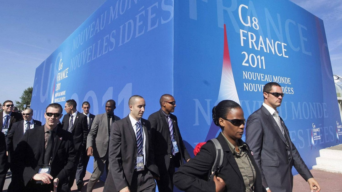 French police officers walk in front of the Deauville Congress Center, in Deauville, western France on Monday, May 23, 2011 where world leaders of the G8 will meet for a summit May 26 and May 27.