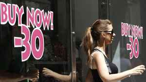 A woman comes out of a shop with discount signs in central Athens.