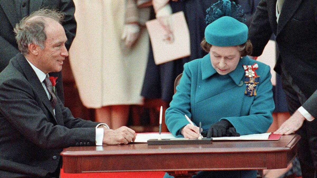 The Queen signs Canada's constitutional proclamation in Ottawa on April 17, 1982 as Prime Minister Pierre Trudeau looks on.