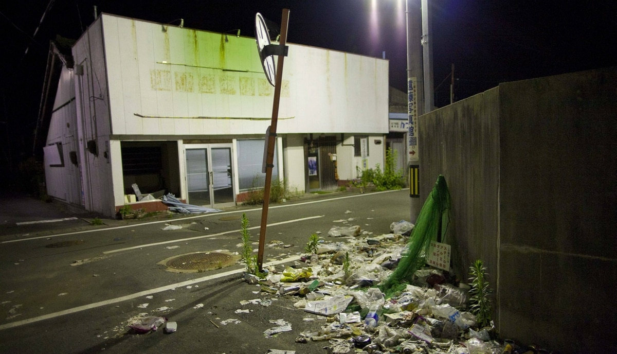 Garbage lies on an abandoned street in Odaka, inside the 20-kilometer exclusion zone around the Fukushima Daiichi nuclear plant, in northeastern Japan, July 24, 2011. A year after the Tsunami, cleanup has begun, but experts say areas inside the nuclear exclusion zone will be difficult to decontaminate.