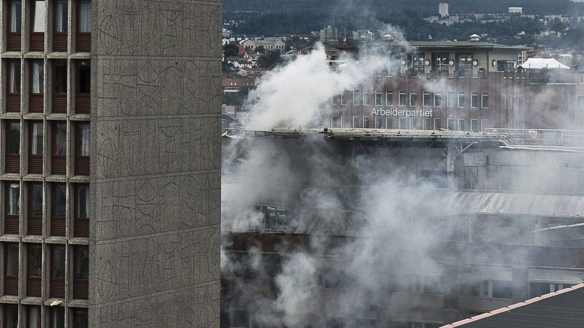 Smoke rises from buildings in Oslo, Norway, at the scene of a large explosion which tore apart several buildings Friday July 22, 2011.