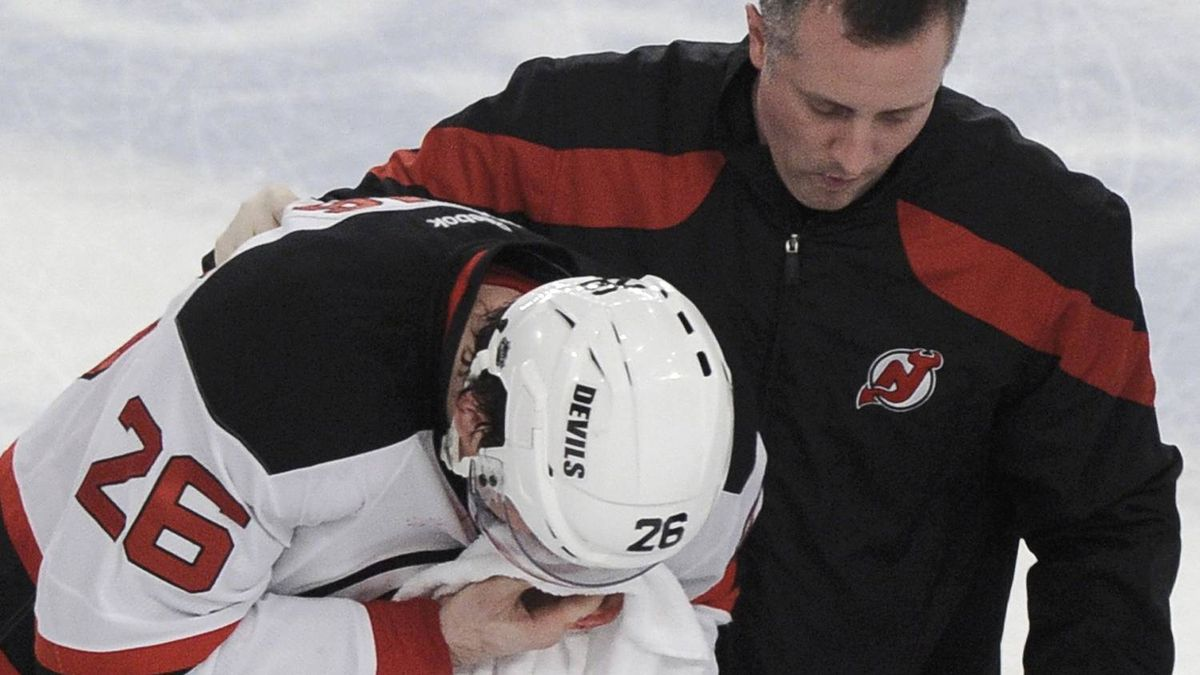 New Jersey Devils' Patrik Elias is taken off the ice by a trainer during the first period of play. REUTERS/Ray Stubblebine