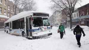 People pass a city bus stuck in the snow, Monday, Dec. 27, 2010 in the Brooklyn borough of New York. A powerful East Coast blizzard menaced would be travelers Monday. Two buses and two sanitation trucks were stuck on the same block in the Park Slope neighborhood of Brooklyn.