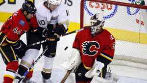Anaheim Ducks' Corey Perry, centre, and Calgary Flames' Chris Butler jostle in front of goalie Miikka Kiprusoff during NHL hockey action in Calgary on Jan. 12, 2012.