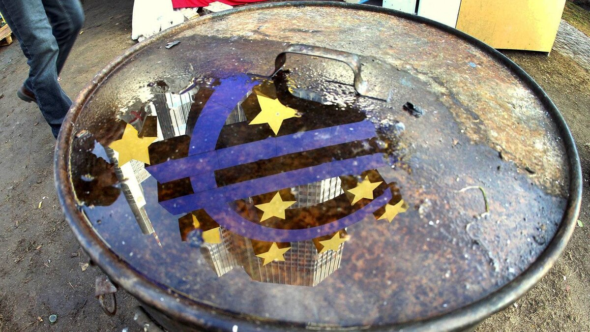 The Euro sculpture is reflected in a puddle on the lid of a bin that stands in the Frankfurt Occupy camp at the European Central Bank in Frankfurt, Germany, Wednesday, Nov.30, 2011