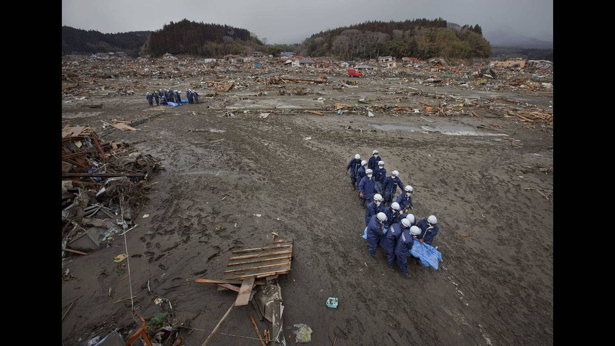 Policemen carry the bodies of victims retrieved from the debris in Rikuzentakata, Iwate Prefecture, days after the area was devastated by a magnitude 9.0 earthquake and tsunami, March 16, 2011.