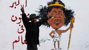 A Libyan man gestures front of a graffiti reading: 'The greatest Crazy of the World' Friday in Tripoli. The death Thursday of Moammar Gadhafi, two months after he was driven from power and into hiding, decisively buries the nearly 42-year regime that had turned the oil-rich country into an international pariah and his own personal fiefdom. AP Photo/Francois Mori