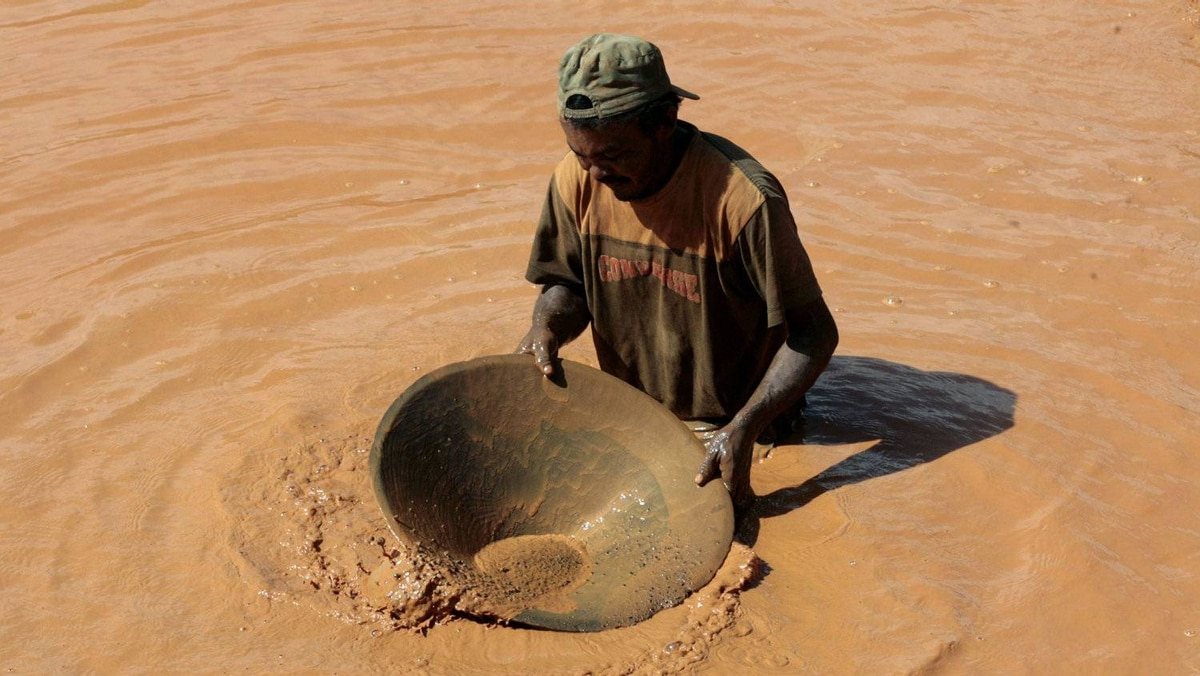 A local miner uses a wooden bowl and mercury to pan for gold near at the village of Las Cristinas in Venezuela.