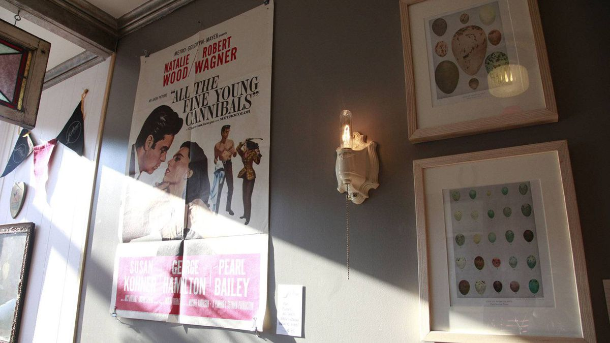 A vintage movie poster hanges on the wall next to two framed photos at the Arthur vintage decor shop in Toronto