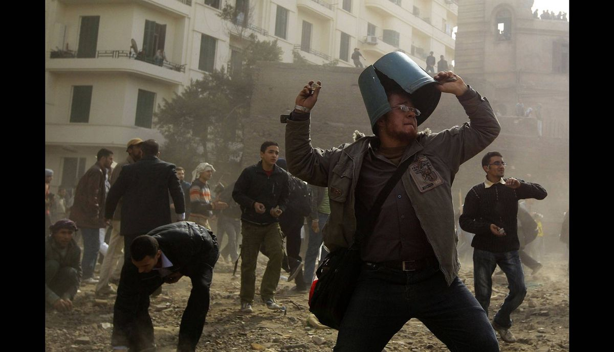 An opposition demonstrator throws a rock during rioting with pro-Mubarak supporters near Tahrir Square in Cairo February 3, 2011.