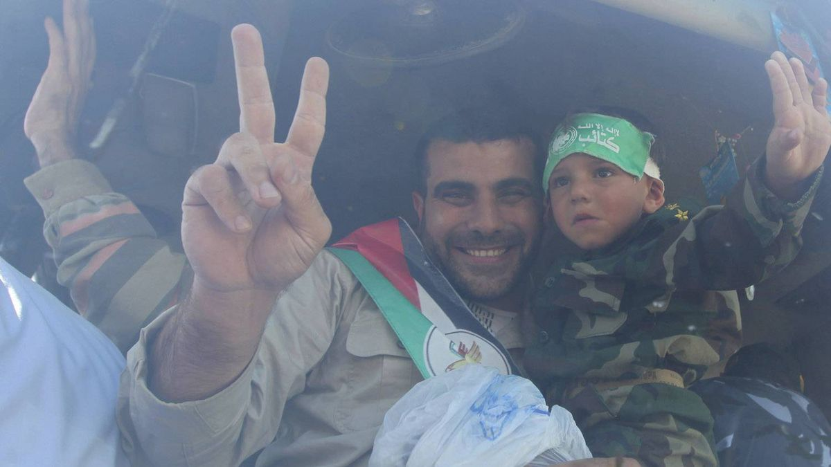 A Palestinian prisoner gestures as he holds his son after arriving at the Rafah crossing with Egypt in the southern Gaza Strip October 18, 2011.