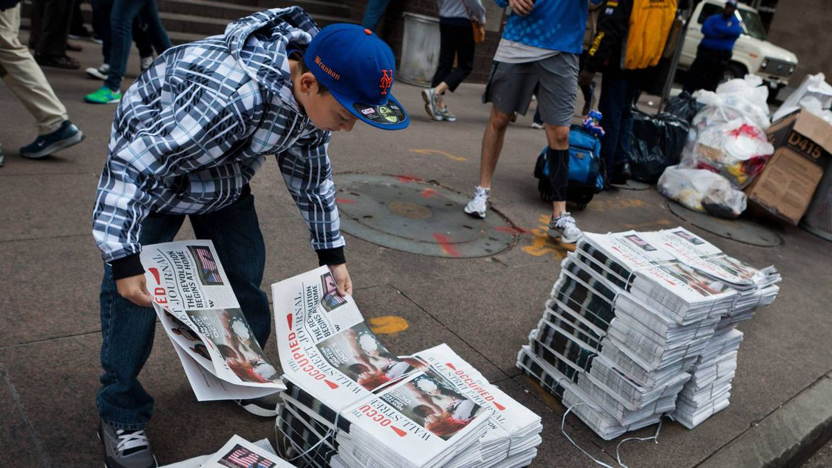 """A pedestrian takes copies of the Occupy Wall Street protest's self-published newspaper """"The Occupied Wall Street Journal, """" in the financial district's Zuccotti park, Sunday, Oct. 2, 2011, in New York."""