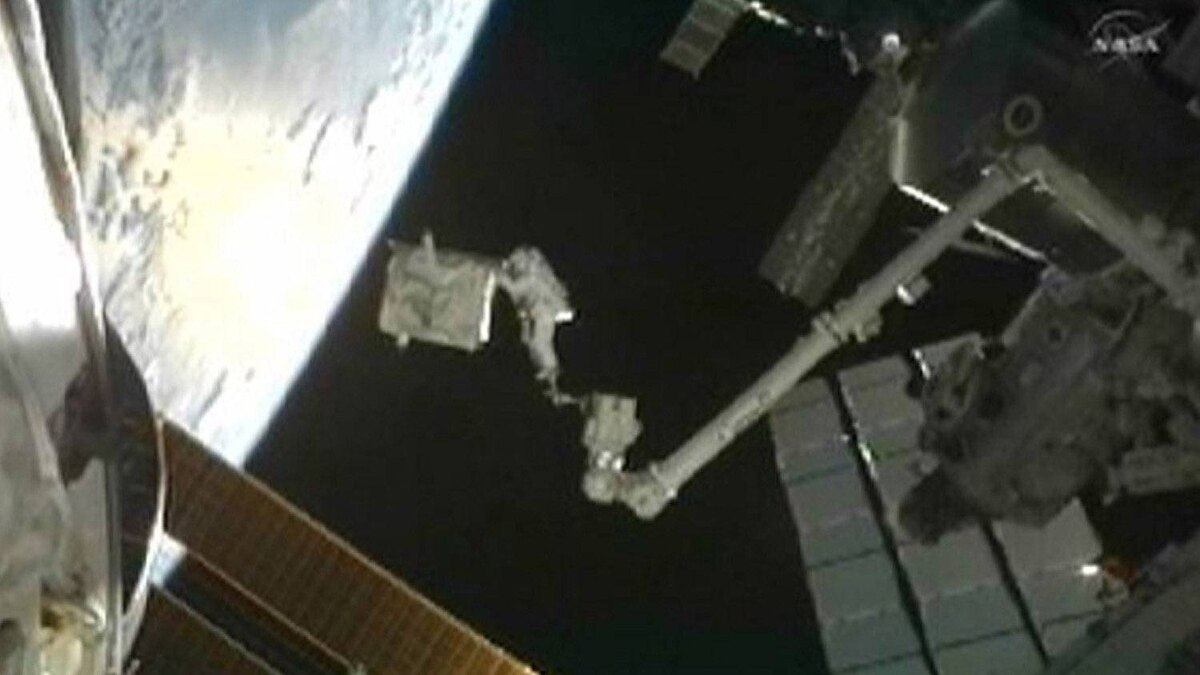 Astronaut Ron Garan holds the pump module as he is moved on the International Space Station's Canadarm2 toward the space shuttle Atlantis' payload bay for the faulty module's return to Earth in this image from NASA TV July 12, 2011.