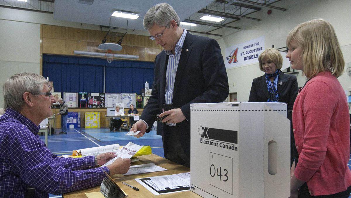 Conservative leader Stephen Harper shows his identification before voting in the Canadian federal election as his wife Laureen (2nd R) and daughter Rachel look in his Calgary, Alberta riding May 2, 2011.