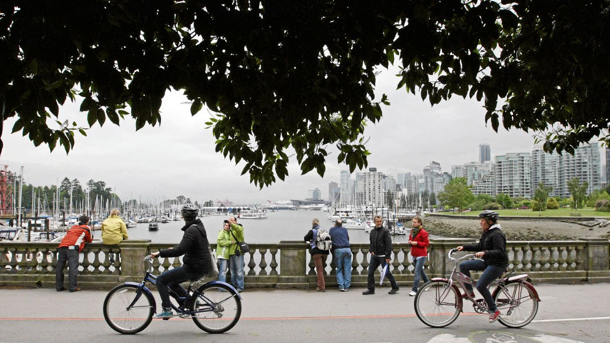 Tourists take photographs as cyclists pass by at Stanley Park in Vancouver, B.C.