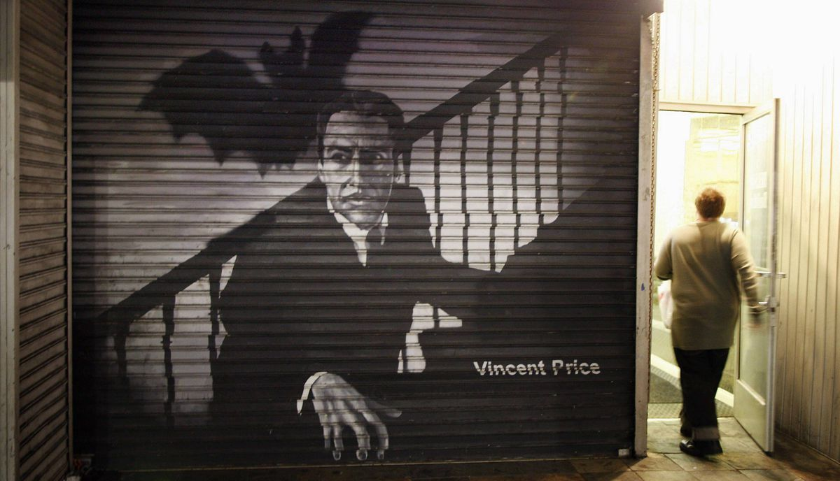 A person enters a door next to an image of horror movie actor Vincent Price on the security door of a business on Hollywood Boulevard in Hollywood, California late February 20, 2012.