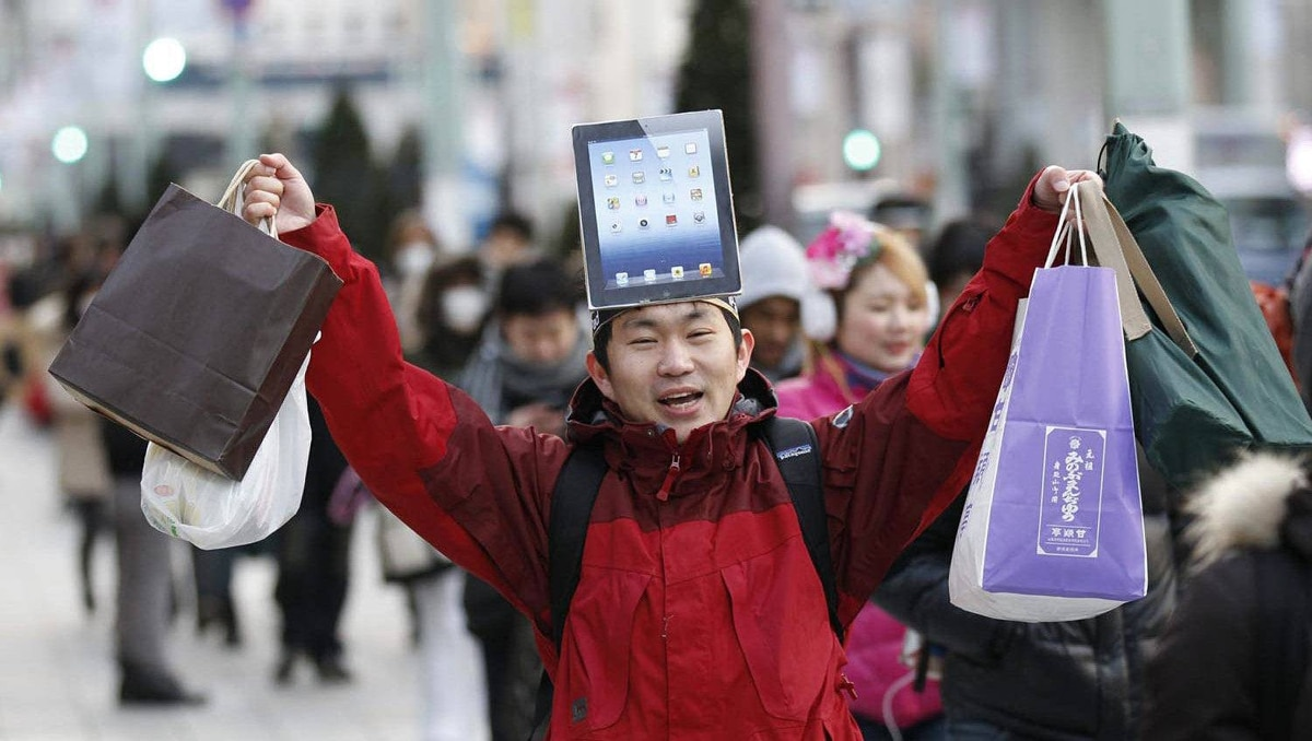 A man wearing a cardboard hat depicting Apple's new iPad waits to purchase the tablet in front of the Apple Store Ginza in Tokyo on March 16, 2012.