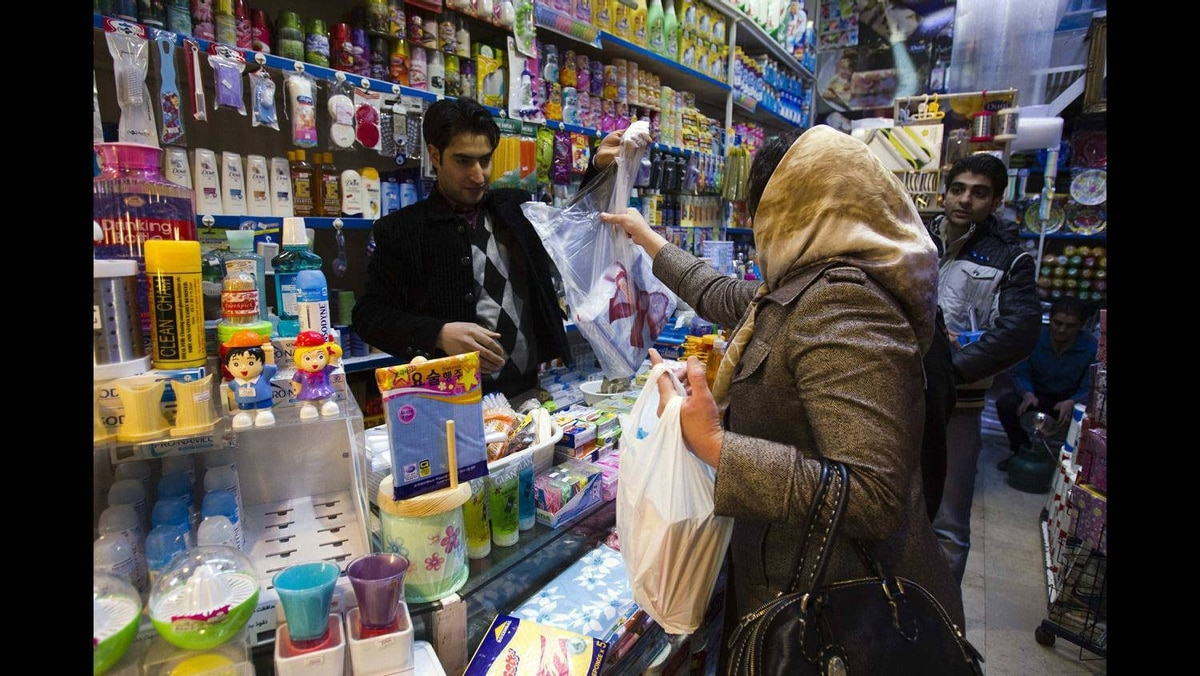 A woman makes a purchase at a store in Tehran January 6, 2012.