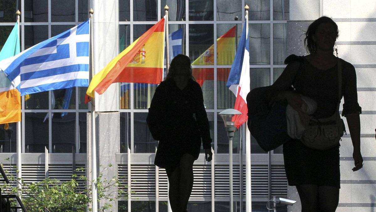 Pedestrians walk near the Greek, Spanish and French national flags outside the European Parliament in Brussels ahead of an EU informal heads of state summit .