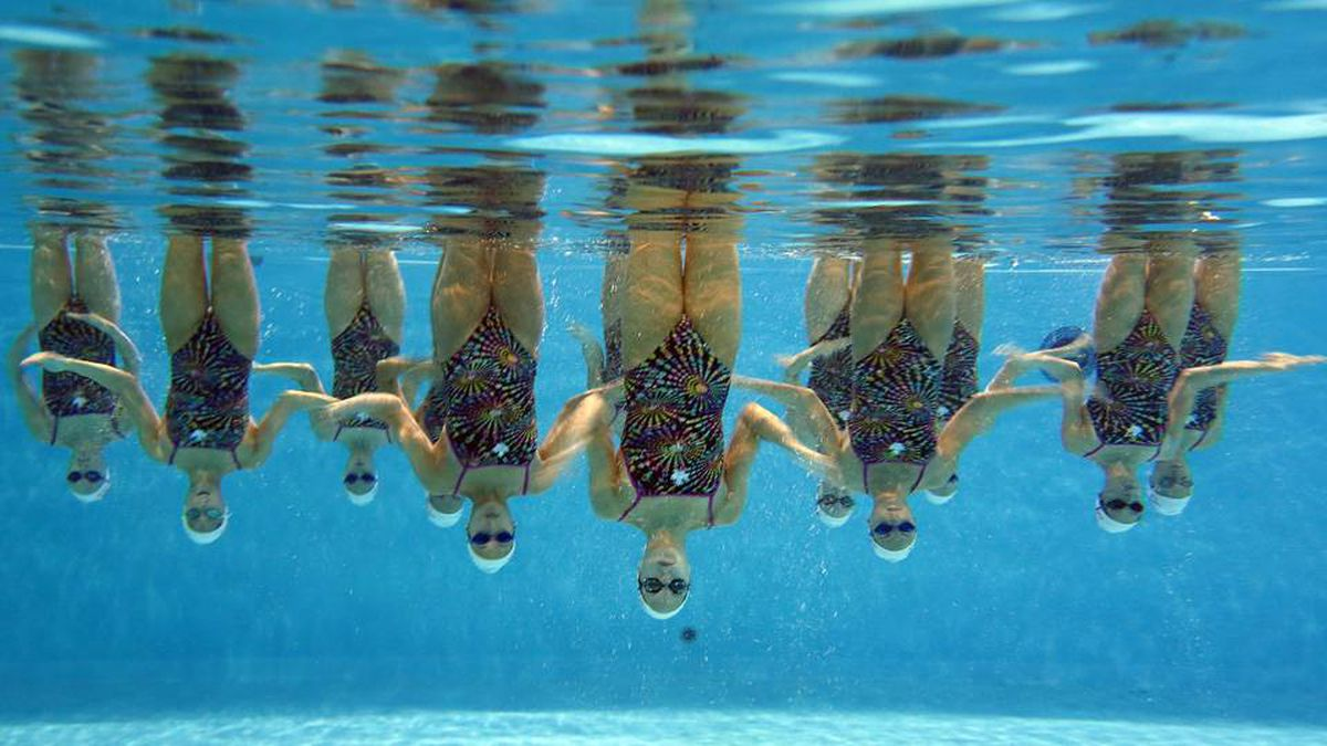 The women skull their arms rapidly while holding a stance upside down as their legs kick above the surface in perfect unison.