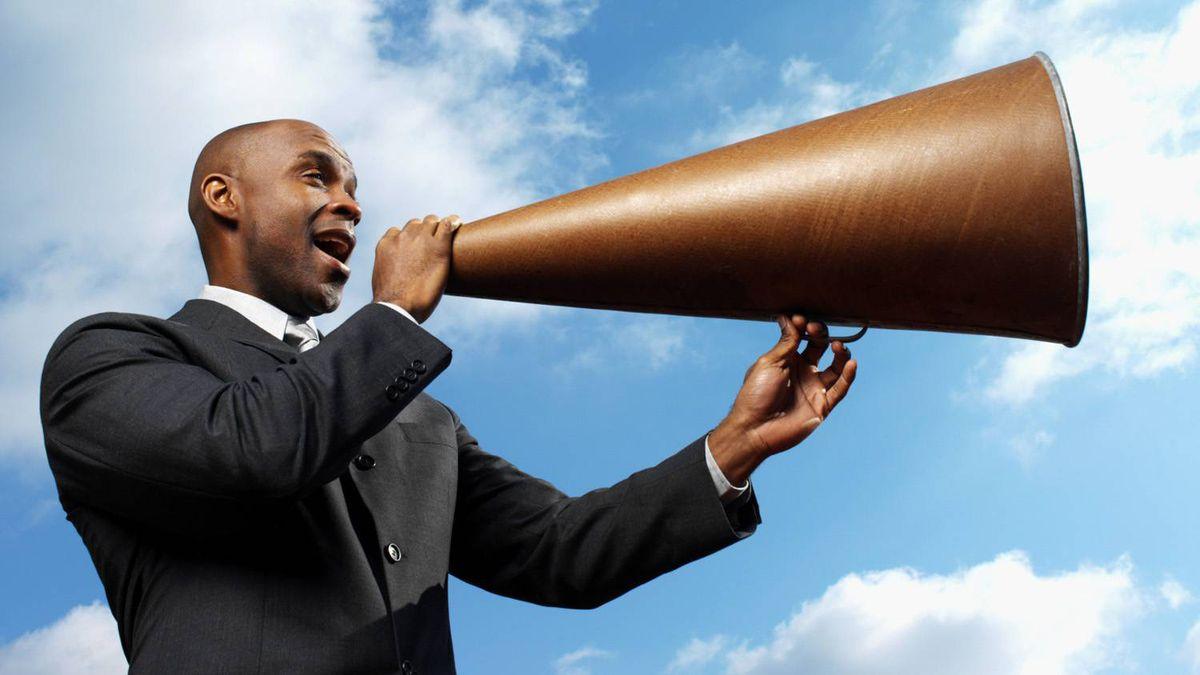 businessman talking through megaphone, low angle view