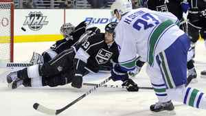 Vancouver Canucks center Henrik Sedin, right, of Sweden scores a goal on Los Angeles Kings goalie Jonathan Quick, left, as defenseman Willie Mitchell defends during the third period of Game 4 in a first-round NHL Stanley Cup playoff series, Wednesday, April 18, 2012, in Los Angeles.