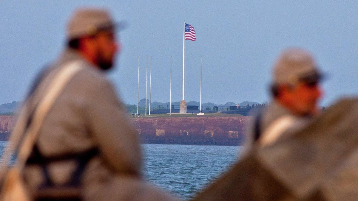 Confederate re-enactors look out at Fort Sumter in Charleston Harbor, from positions in Fort Moultrie early on April 12, 2011 in Charleston, SC.