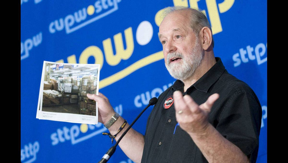 CUPW national president and chief negotiator Denis Lemelin holds up a picture of mail sitting at a Canada Post facility as he speaks with the media in Ottawa. The union representing postal workers says Canada Post wants to provoke a national strike in a bid to encourage the federal government to introduce back-to-work legislation.