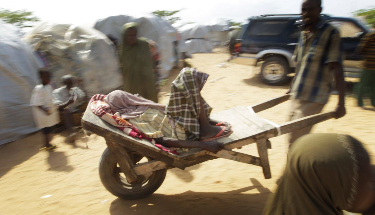 A man transports another ill person past the MSF vaccination clinic toward the Banadir Hospital.