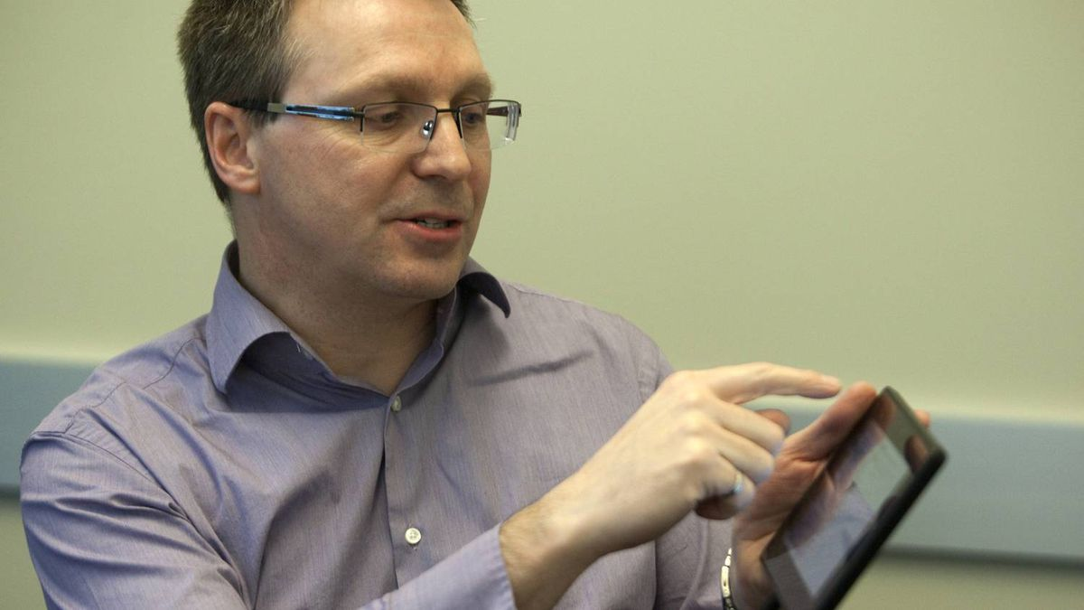 David J. Smith, senior vice-president of mobile computing, holds a BlackBerry PlayBook as he speaks about the upcoming software revamp.