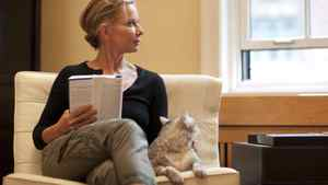 Writer and O Magazine editor Susan Casey reads with her cat, Mouse, in her living room in New York City.
