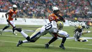 Deon Beasley of the Winnipeg Blue Bombers attempts to tackle Andrew Harris of the B.C. Lions during the first half.