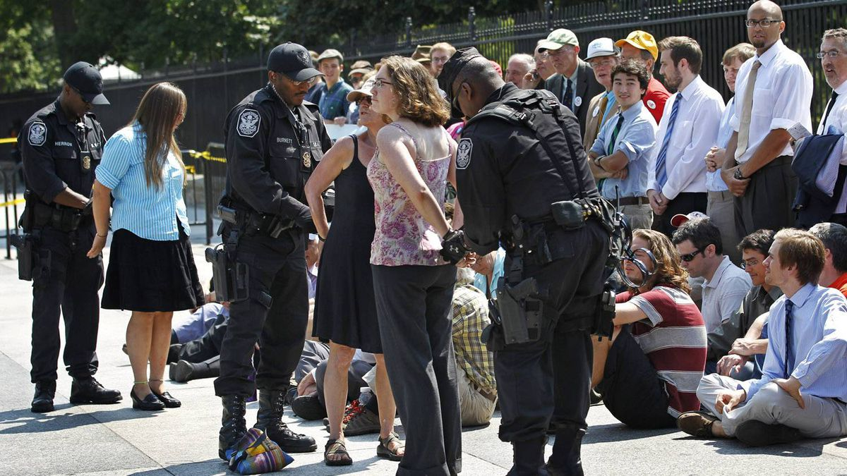 U.S. Park Police officers handcuff and arrest protestors over a proposed pipeline to bring tar sands oil to the U.S. from Canada, in front of the White House in Washington, Saturday, Aug. 20, 2011.