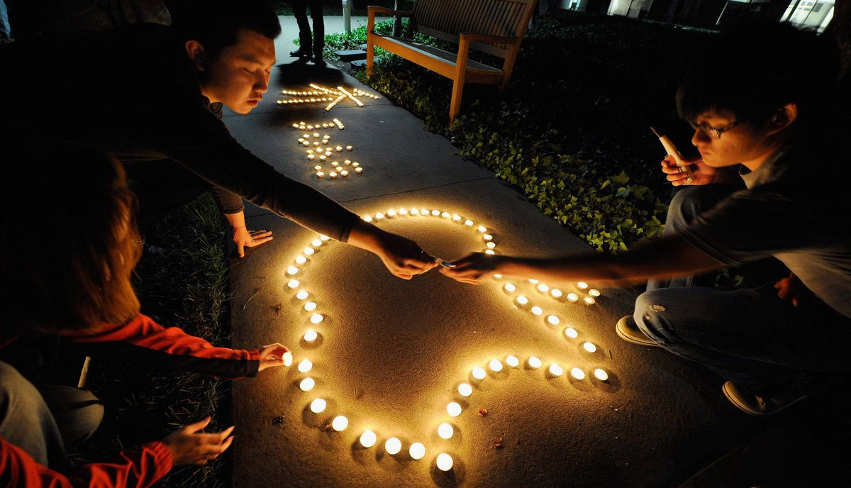 Chinese exchange students from nearby De Anza College use candles to create the Apple logo and Steve Jobs' last name in Chinese characters at a makeshift memorial for Steve Jobs at the Apple headquarters on October 5, 2011 in Cupertino, California.