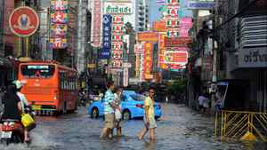 Residents walk in floodwaters along a street in the Chinatown section of Bangkok on Oct. 28, 2011.