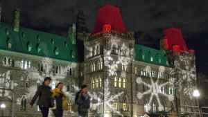 Christmas lights reflect on the walls of the Parliament buildings.