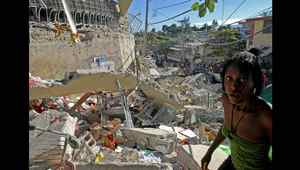 Haitians pass destroyed buildings on Jan. 13, 2010 in Port-au-Prince.