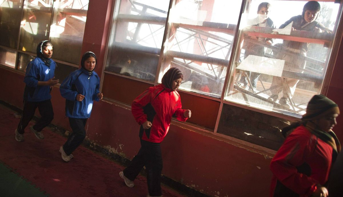 Afghan women boxers run during a practice session as boys watch from outside a boxing club in Kabul December 28, 2011.