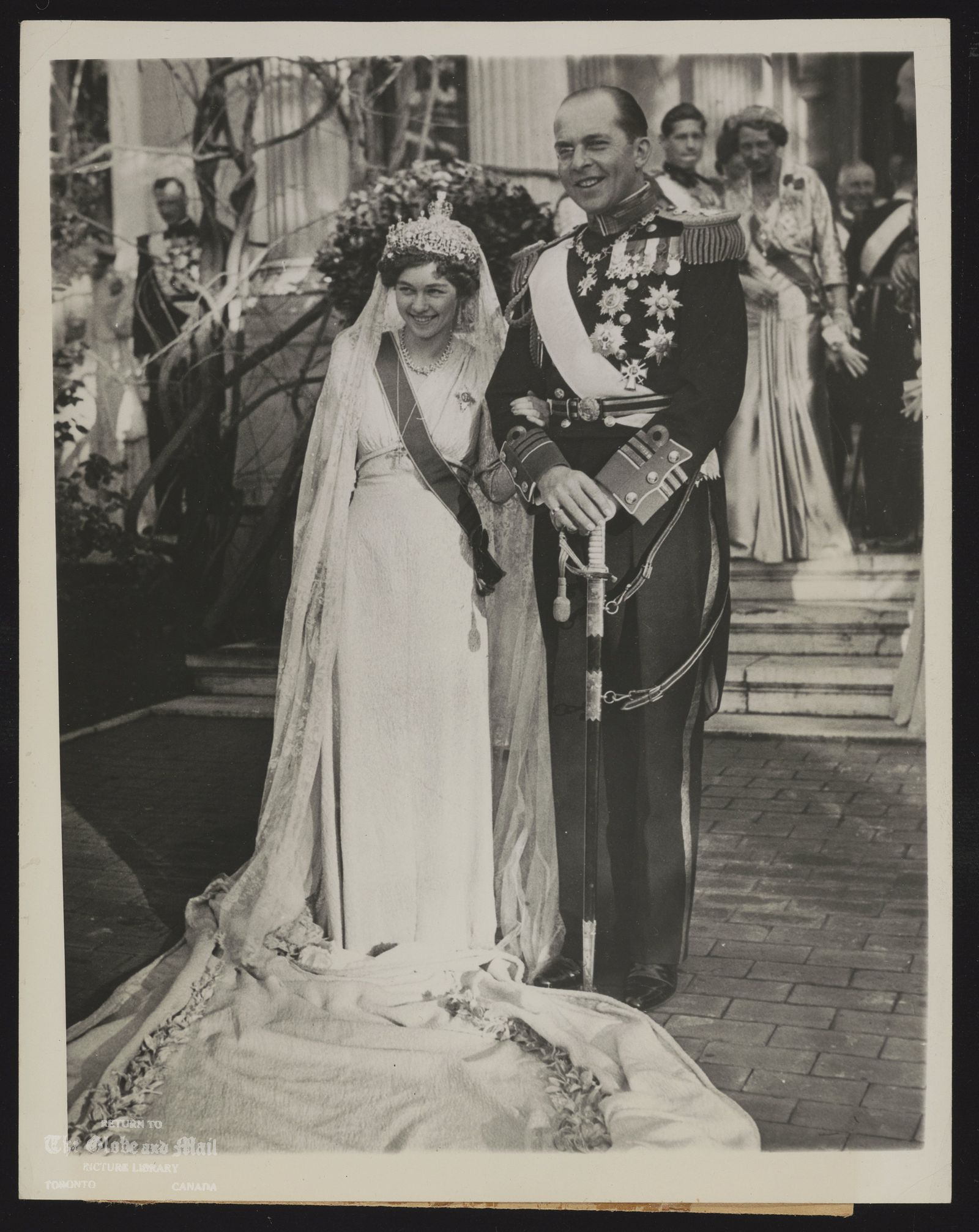 25605 ASSOCIATED PRESS PHOTO FROM NEW YORK CAUTION: USE CREDIT EUROPE'S LATEST ROYAL WEDDING SHOWN OUTSIDE THE ROYAL PALACE IN ATHENS, GREECE, JANUARY 9, AFTER THE CEREMONY ARE CROWN PRINCE PAUL OF GREECE AND HIS BRIDE, PRINCESS FREDERIKA LUISE OF BRUNSWICK, A GRANDDAUGHTER OF THE EX-KAISER OF GERMANY AND A GREAT-GREAT-GRANDDAUGHTER OF QUEEN VICTORIA OF ENGLAND. THE WEDDING WAS ATTENDED BY MEMBERS OF MANY OF EUROPE'S ROYAL FAMILIES. ASSOCIATED PRESS PHOTO 1/19/38 OR 10:50AEST LON A B C HAVANA HARTFORD MONTREAL 70