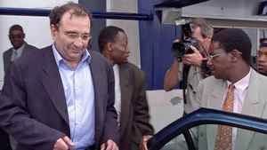 Ari Ben Menashe is hustled into a car by Zimbabwean security personnel shortly after his arrival in Harare on Feb. 22, 2002.