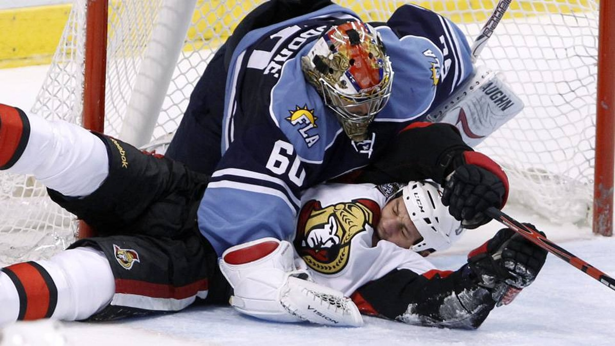 Ottawa Senators center Zenon Konopka, bottom, collides with Florida Panthers goalie Jose Theodore during the second period of an NHL hockey game, Sunday.
