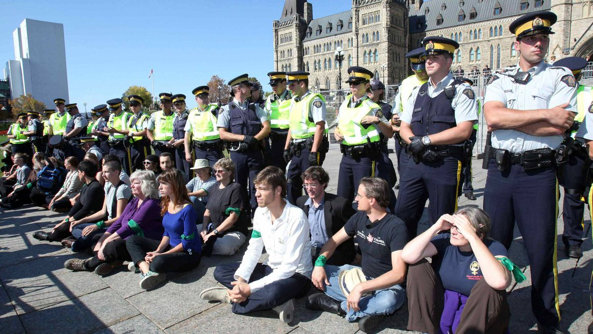 """Demonstrators stage a """"sit in"""" after crossing a police barricade during a protest against the Keystone XL pipeline on Parliament Hill in Ottawa September 26, 2011."""
