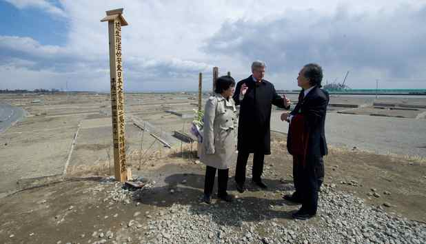 Prime Minister Stephen Harper, middle, and Minister of International Cooperation Bev Oda, left, talk with Mayor Iso Sasaki as they visit the Yuriage Shrine in the coastal region of Sendai, Japan on Monday, March 26, 2012. The area was heavily impacted by the March 11, 2011, earthquake and tsunami.