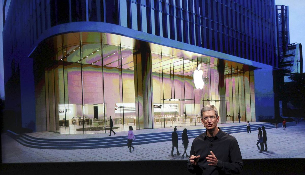 Apple CEO Tim Cook speaks in front of an image of the Shanghai Apple Store at Apple headquarters in Cupertino