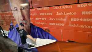 Jordan Blancher applies adhesive wrap covering to a Canada Coach charter bus for NDP leader Jack Layton March 23, 2011 in preparation for a looming federal election.