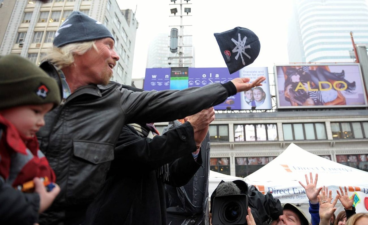 Sir Richard Branson tosses a Virgin Mobile toque to the crowd during an event at Yonge and Dundas Square in Toronto.